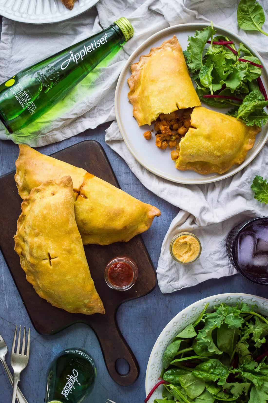 Vegan curried vegetable pasties on a grey background with salad and Appletiser.