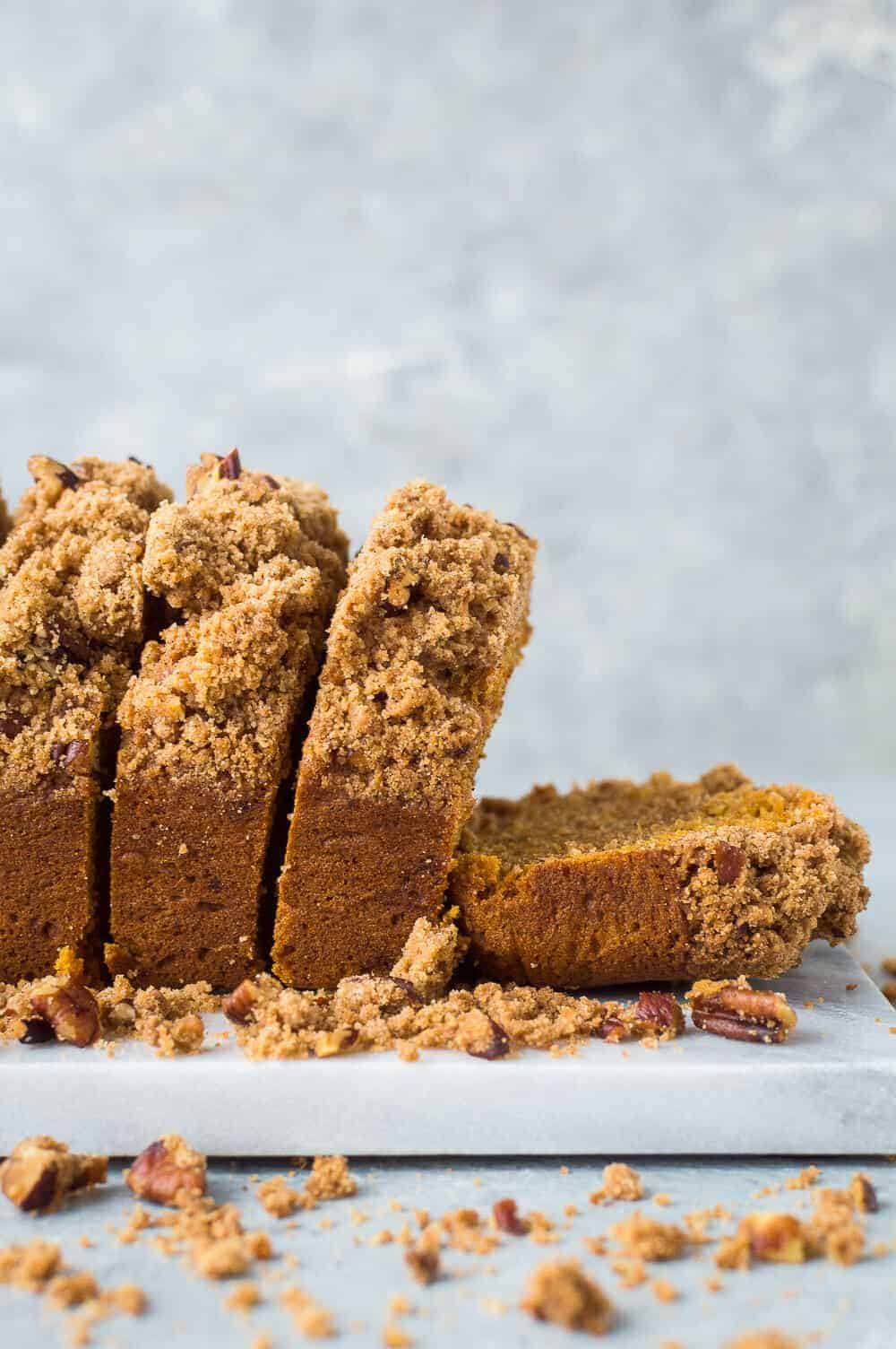 A side shot of sliced vegan sweet potato loaf cake with pecan streusel topping on a marble board and grey background.