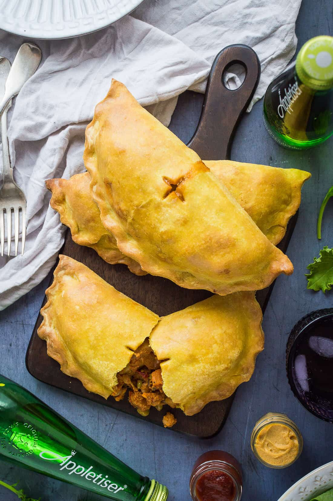 Curried vegetable pasties on awooden board with bottles of Appletiser.