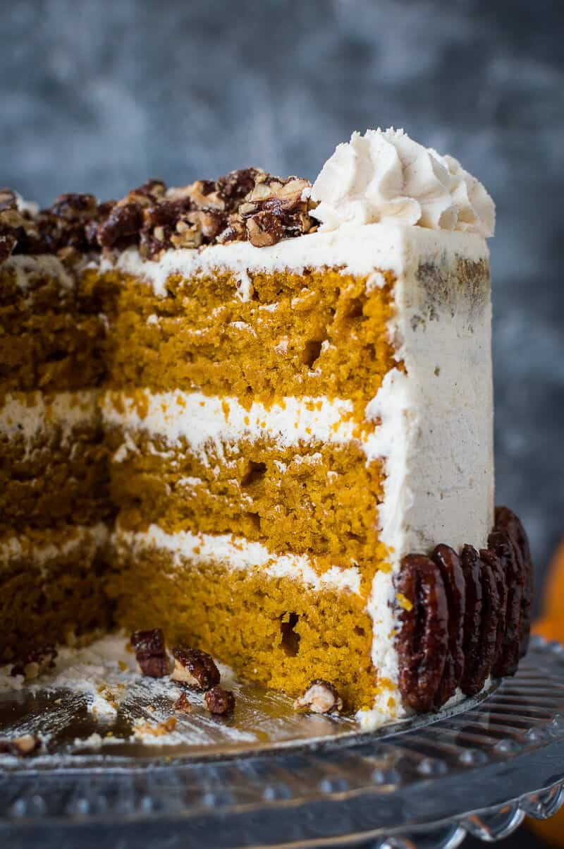 Close up of the crumb of sliced vegan pumpkin cake with maple pecans and cinnamon buttercream on a glass cake stand.