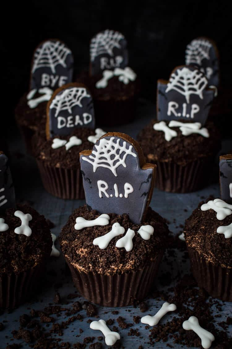 graveyard cupcakes - vegan chocolate cupcakes topped with decorated gingerbread tombstones, oreo soil and vegan royal icing bones.