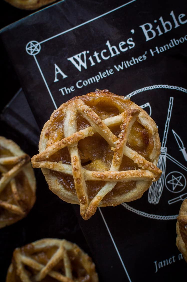 A mini, pentagram topped vegan apple pie on top of a witches' bible book.