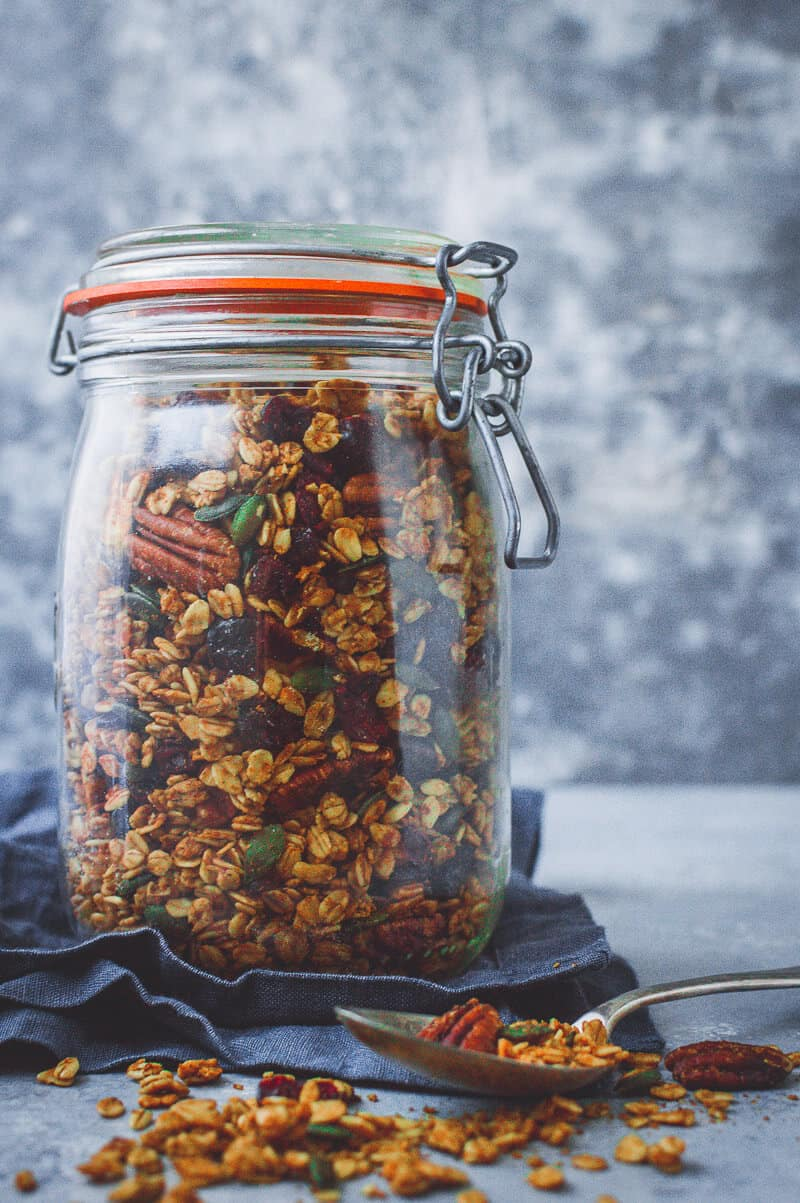 A glass jar full of pumpkin spice granola on a grey background