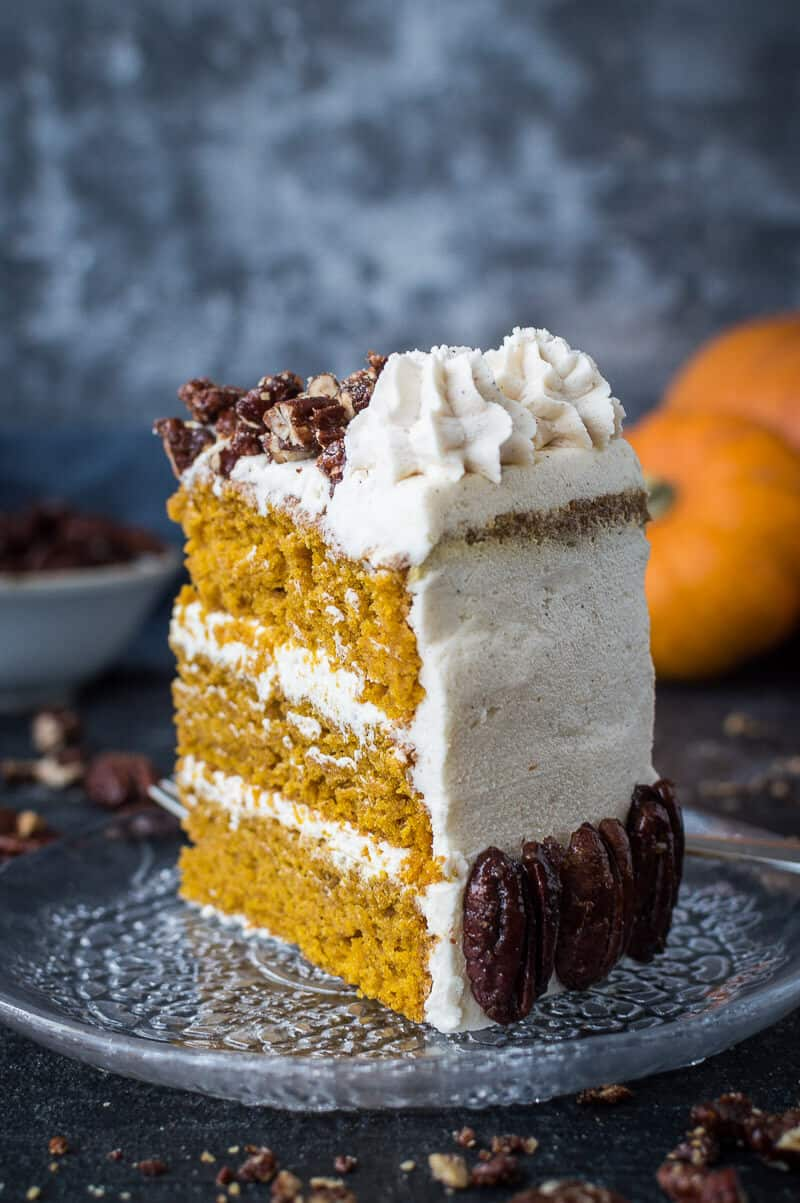A slice of vegan pumpkin cake with maple pecans and cinnamon buttercream on a glass plate with mini pumpkins and pecans in the background.