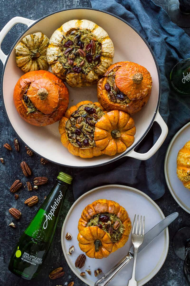 Cranberry and pecan wild rice stuffed mini roastedpumpkins in a dish and on plates on a dark background.