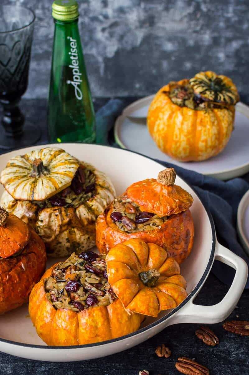 Stuffed mini pumpkins in a cream dish with Appletiser in the background.