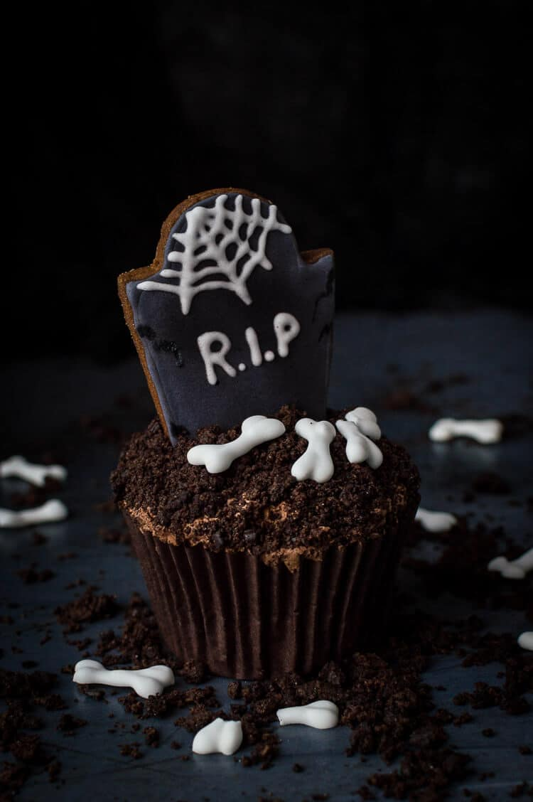 A single vegan tombstone cupcake on a dark background surrounded by Oreo soil and vegan royal icing bones.