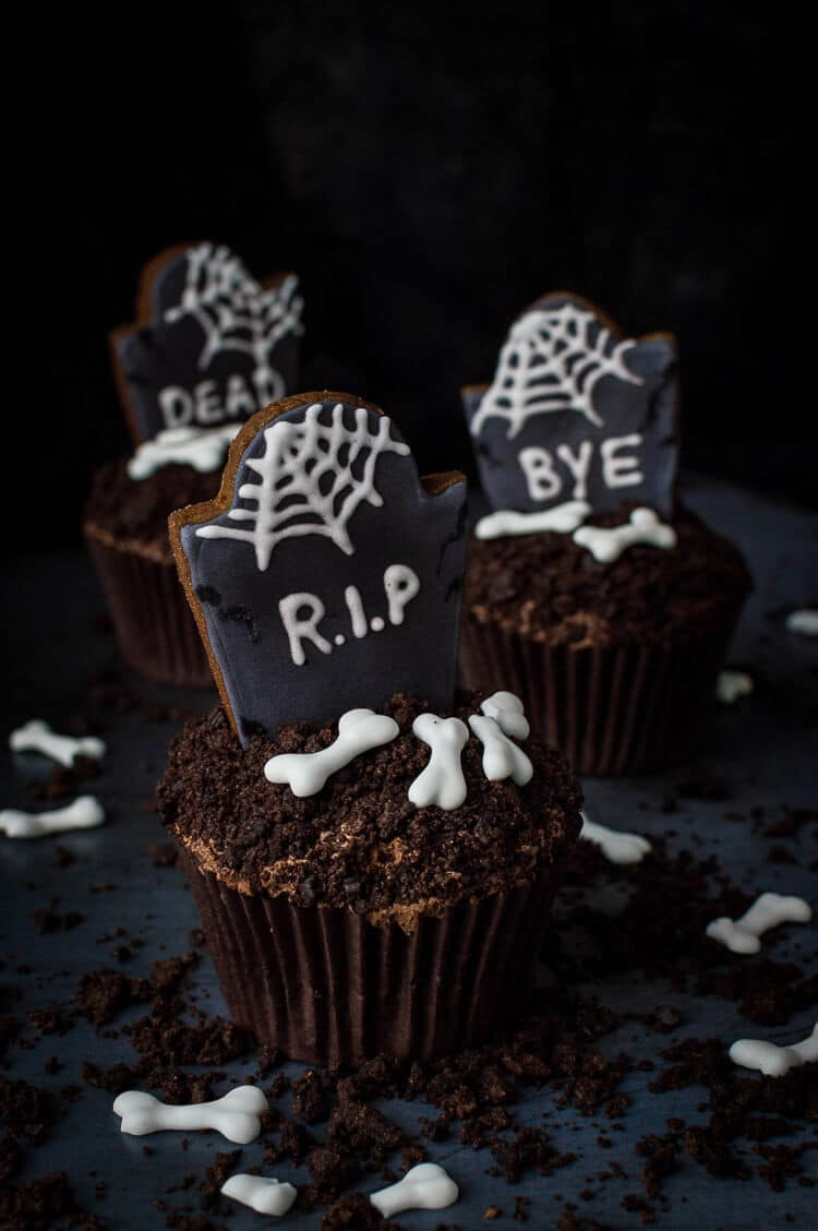 Tombstone cupcakes for Halloween - these impressive chocolate graveyard cupcakes with gingerbread tombstones, cookie dirt and royal icing bones are seriously spooky, utterly delicious and totally vegan! Step by step photos included. #vegan #Halloween #cupcakes #chocolate