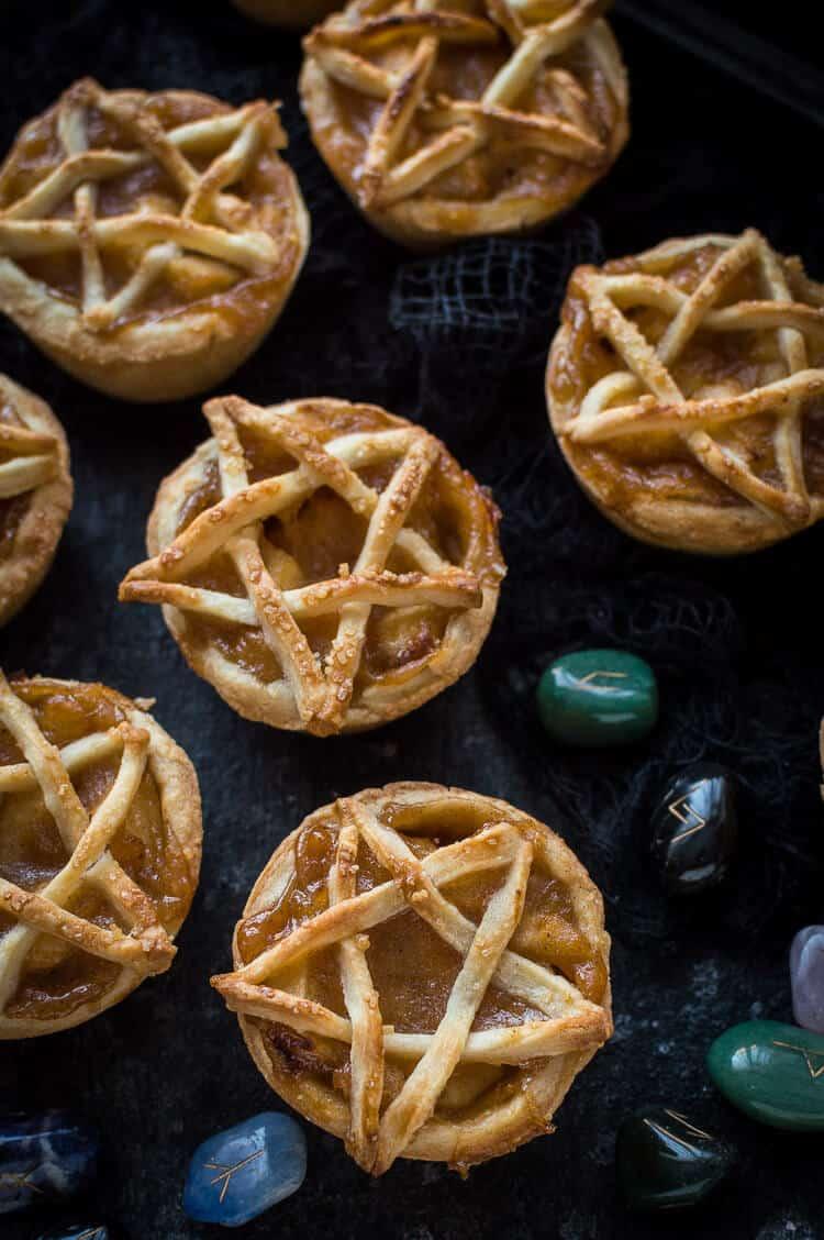 Mini pentagram topped vegan apple pies on a black background with runestones.