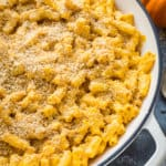 Close up of a pan of vegan pumpkin mac and cheese topped with crispy garlic breadcrumbs.