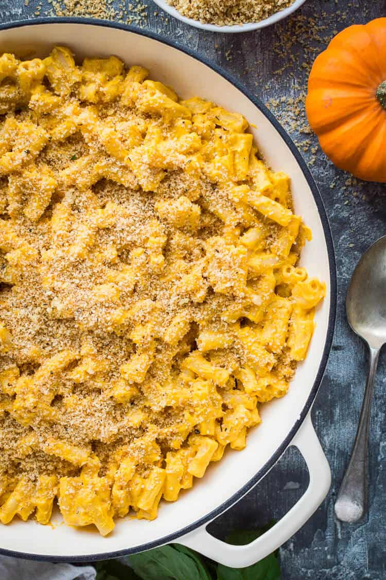 Close up of a pan of vegan pumpkin mac and cheese on a grey background.