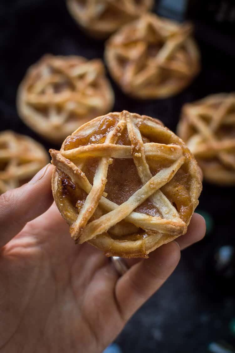 A mini, pentagram topped vegan apple pie being held.