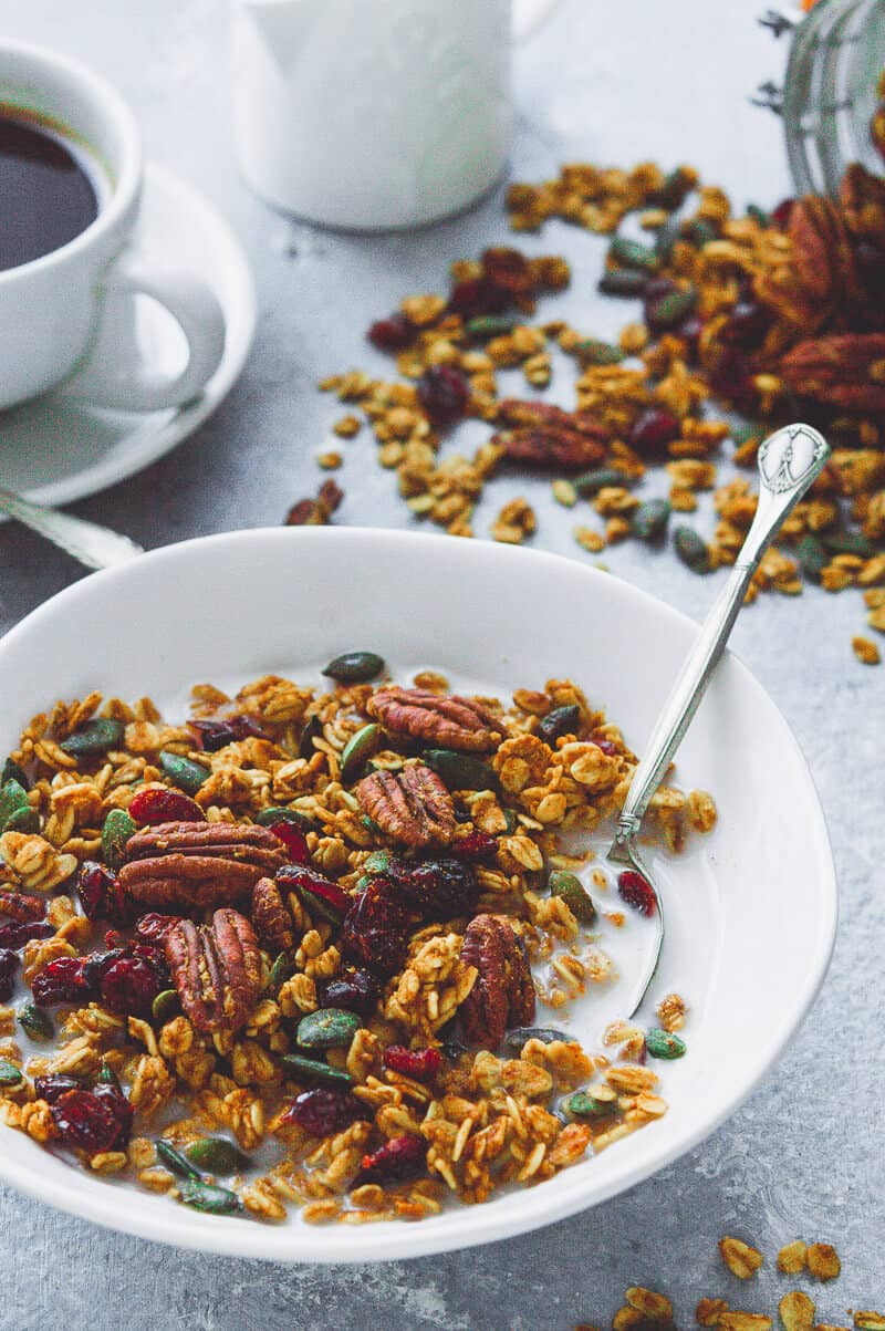 Close up of a bowl of vegan pumpkin spice granola with milk, with coffee and spilled granola in the background.