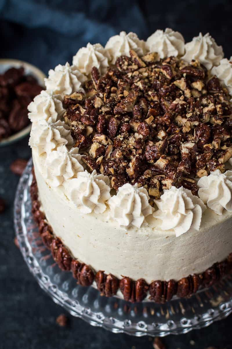 Close up of the top of vegan pumpkin cake topped with chopped maple pecans and blobs of cinnamon buttercream.