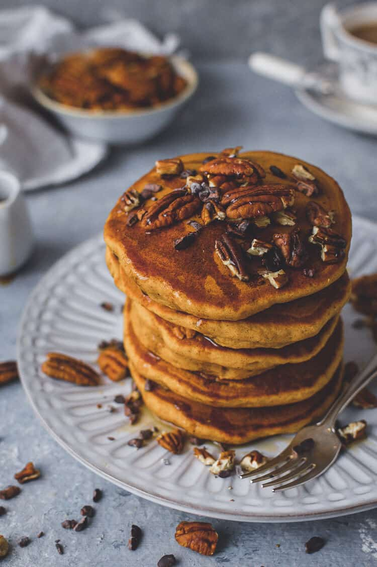 A stack of fluffy vegan pumpkin pancakes on a white plate topped with maple syrup, pecans and cacao nibs.