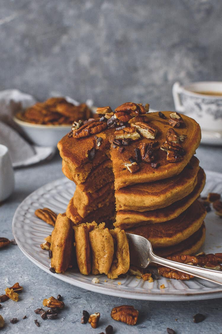 A stack of fluffy vegan pumpkin pancakes topped with maple syrup, pecans and cacao nibs with a forkful taken out.