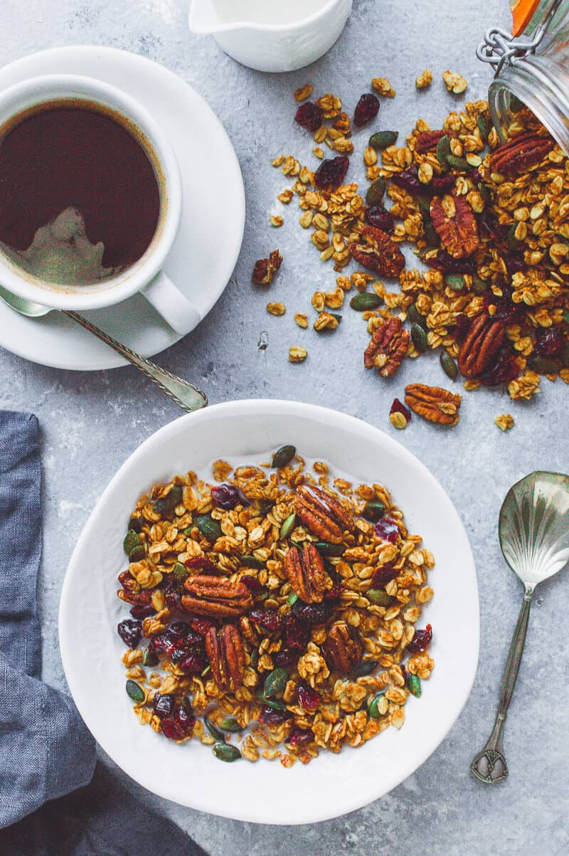A bowl of vegan pumpkin spice granola with coffee, a jug of milk and a jar of spilled granola.