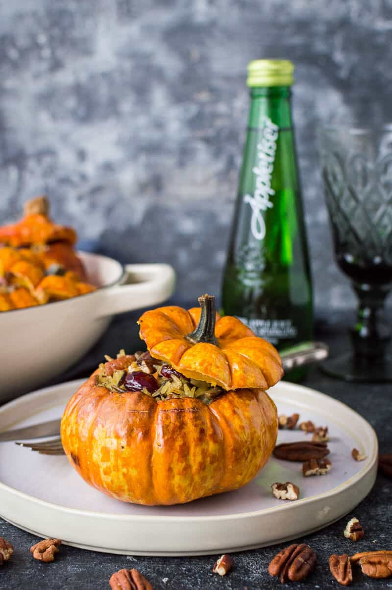 A stuffed mini pumpkin on a plate with a bottle of Appletiser and a glass in the background.