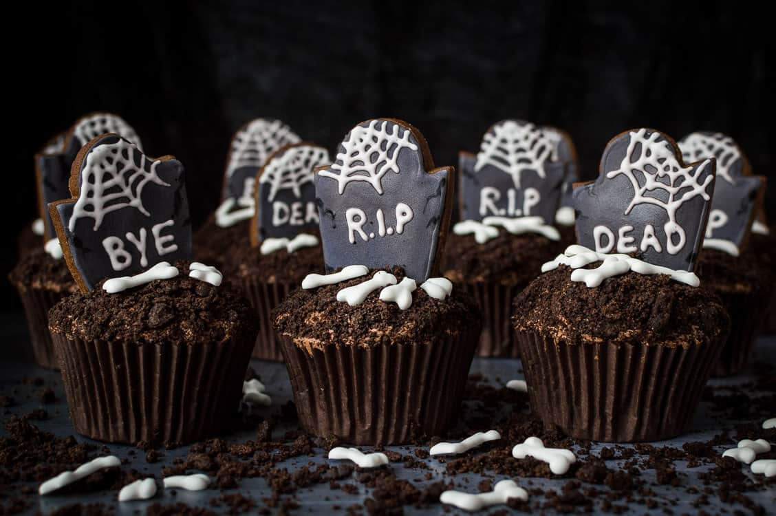 Vegan graveyard cupcakes in a row on a dark background