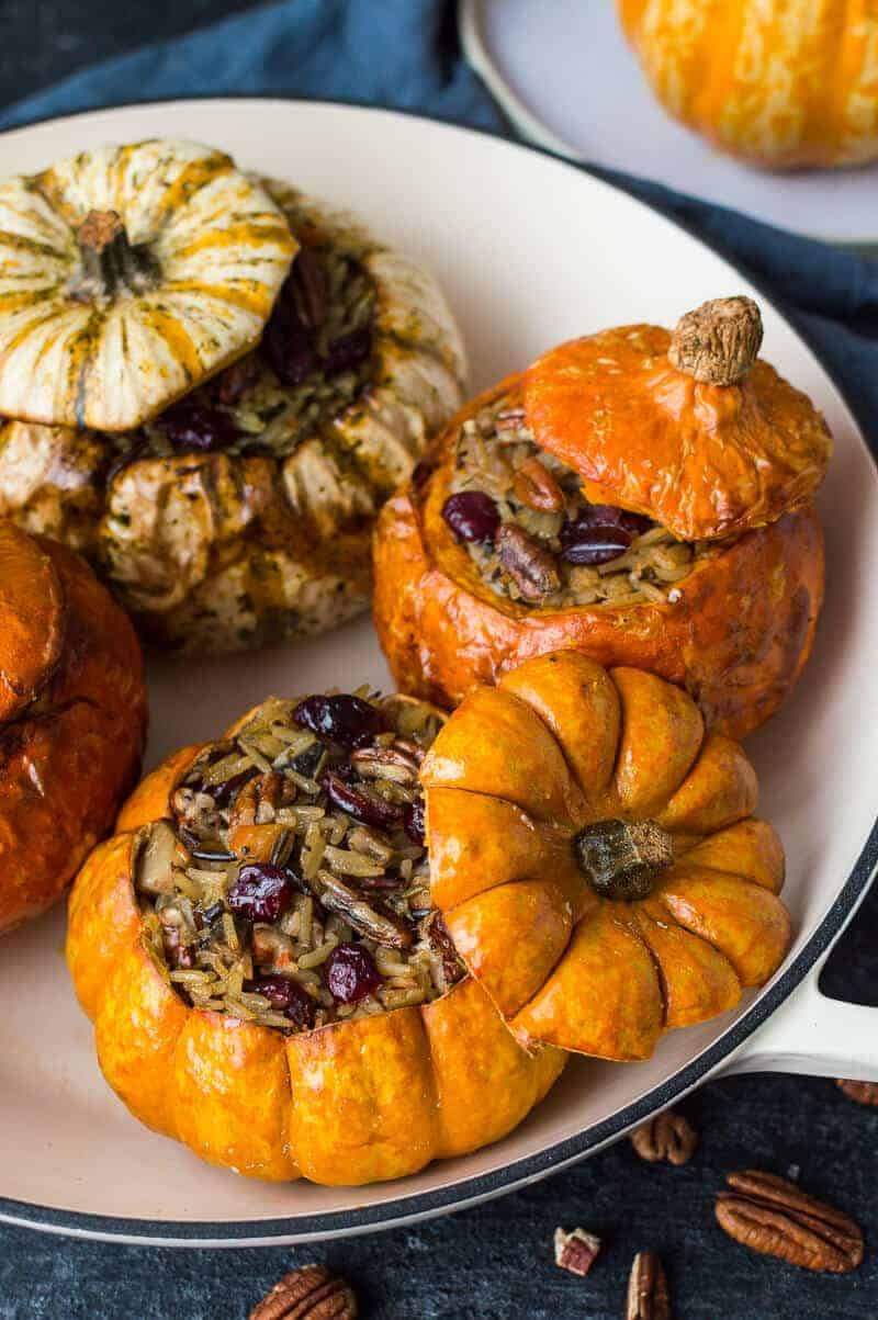 Stuffed mini pumpkins with cranberry and pecan vegetable wild rice in a casserole dish. Vegan and gluten free.