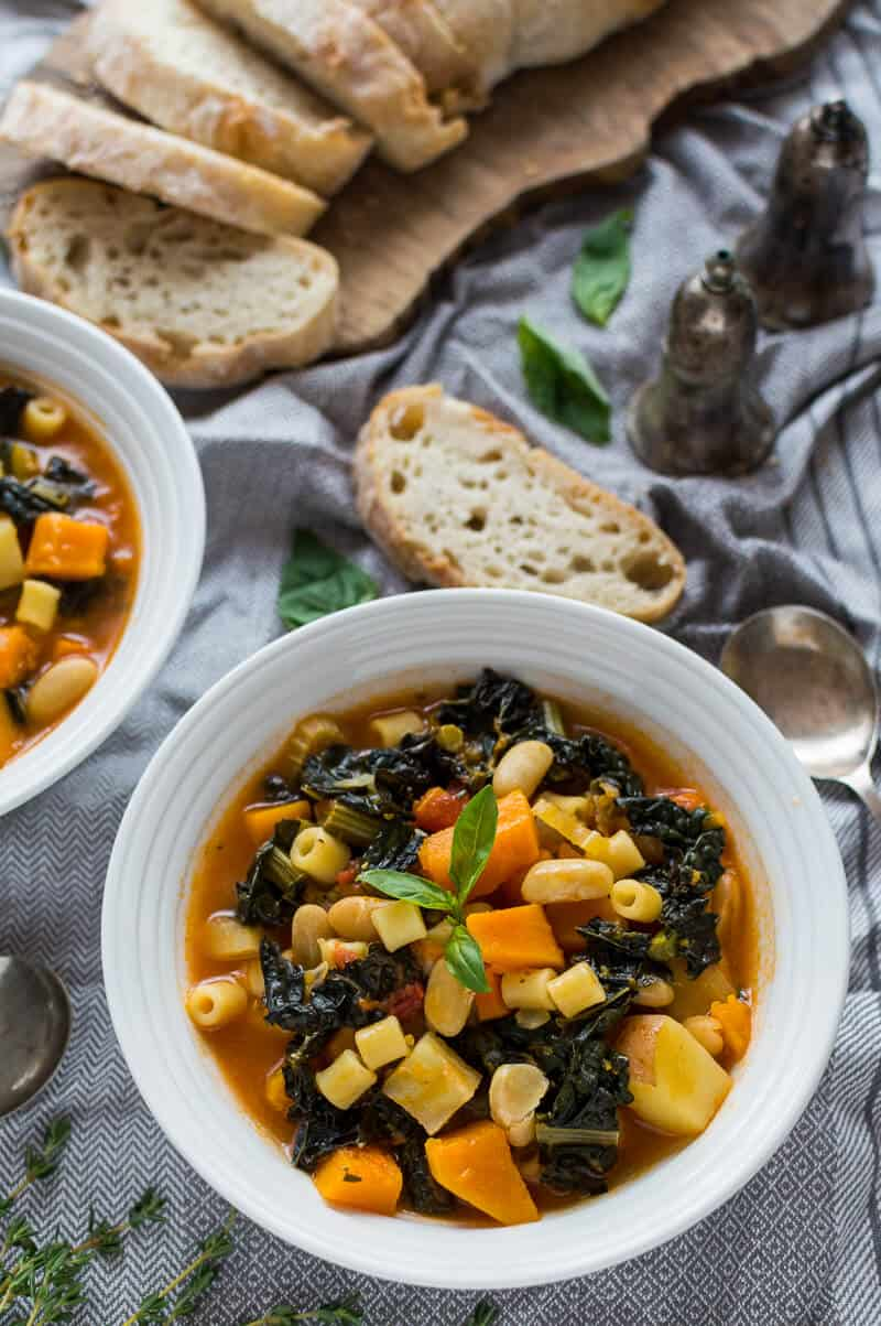 A white bowlful ofvegan Autumn minestrone soup on a grey tablecloth with sliced ciabatta.