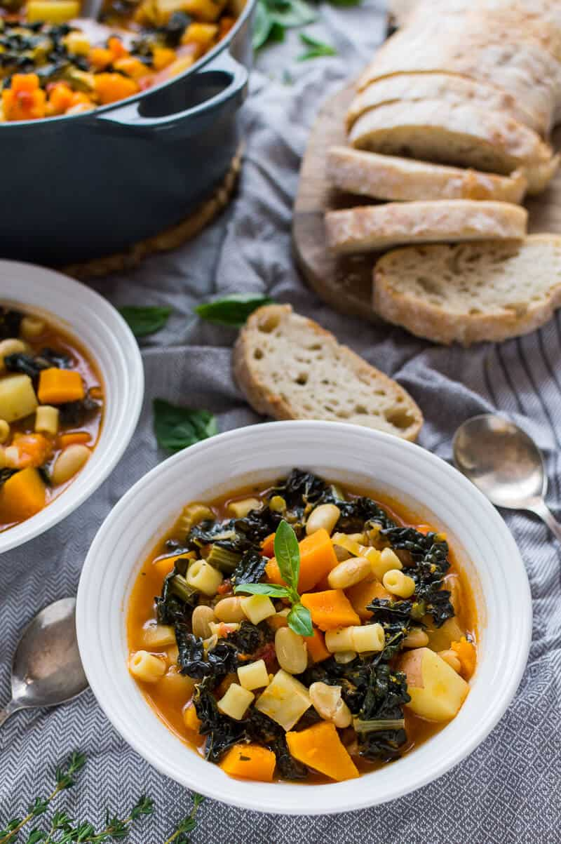 A bowl of Autumn minestrone soup on a grey tablecloth with ciabatta and a pan of soup in the background.