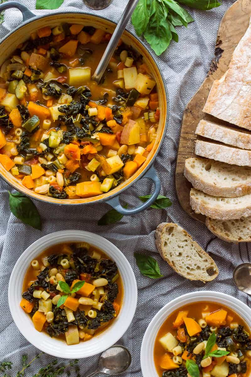 A pan of vegan autumn minestrone soup with two bowlfuls and sliced ciabatta on a grey tablecloth.