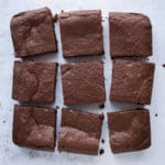 Nine vegan mulled wine brownie squares on a grey background.