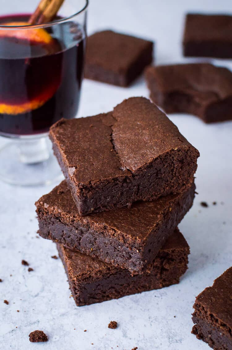 A stack of three fudgy vegan mulled wine brownies with a glass of mulled wine in the background.