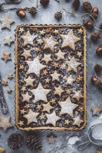 Starry mince pie tart - an attractive twist on traditional mince pies. Shortcrust pastry filled with vegan friendly mincemeat and topped with cinnamon shortbread stars. Perfect as a festive centrepiece!