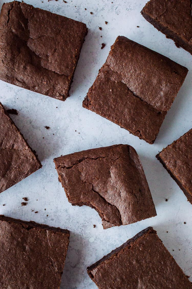 Vegan mulled wine brownies on a grey background; one with a bite taken out.