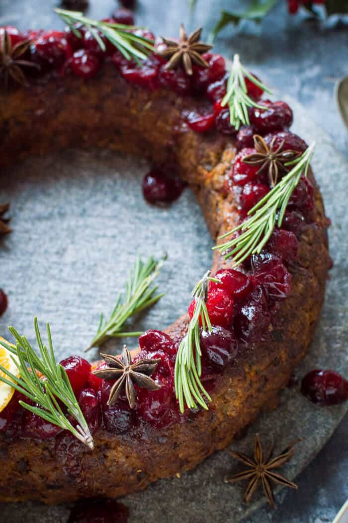 Close up of festive vegan nut roast wreath topped with cranberry sauce, rosemary sprigs and spices.