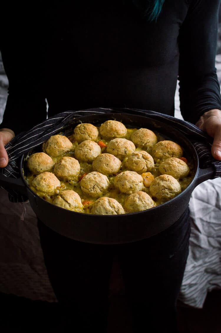A black cast iron pan of vegan vegetable and pearl barley stew topped with herby dumplings being held by a person dressed in black.