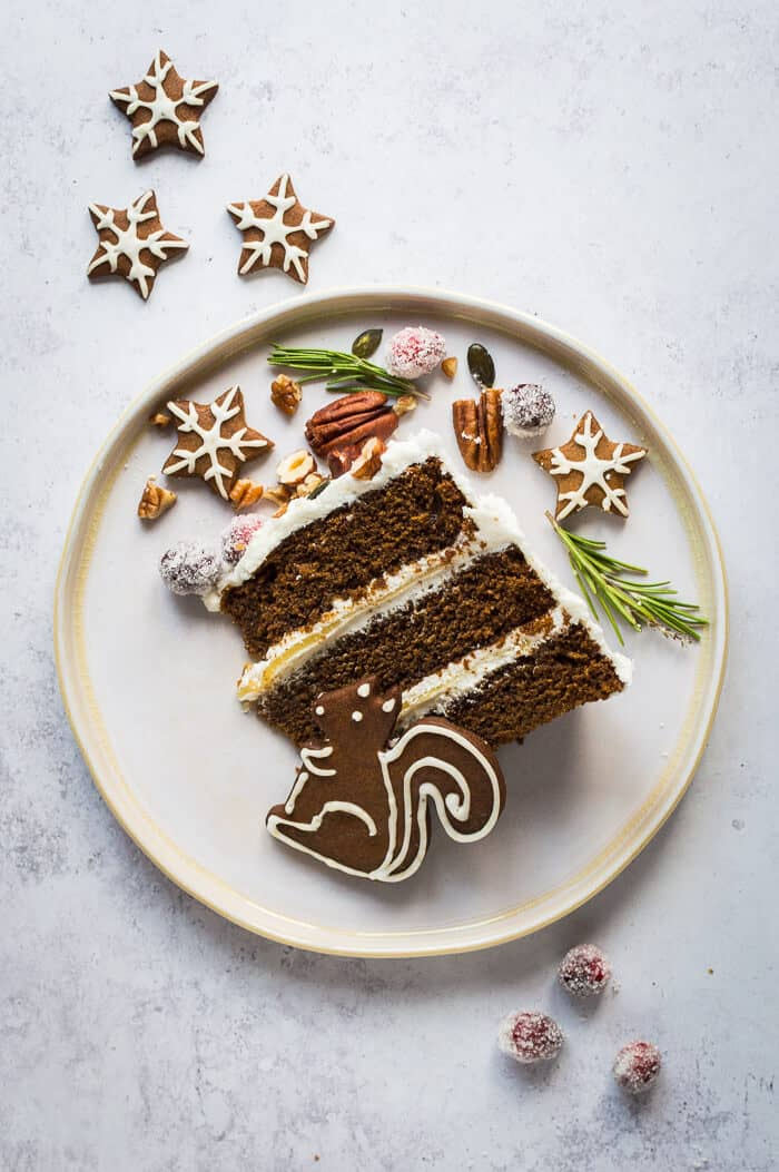 A slice of vegan ginger layer cake with vegan gingerbread woodland animal cookies, sugared cranberries, rosemary, nuts and seeds.