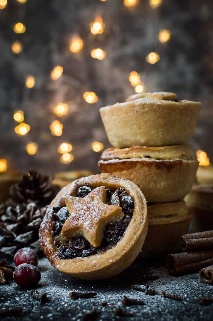 A stack of vegan mince pies with fruit filling and coconut oil pastry in a Christmas scene.