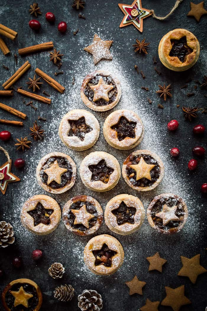 Vegan mince pies with coconut oil pastry arranged in a Christmas tree shape and sprinkled with icing sugar on a dark background with festive decorations.