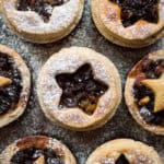 a close up of vegan mince pies with coconut oil pastry dusted with icing sugar on a black background.