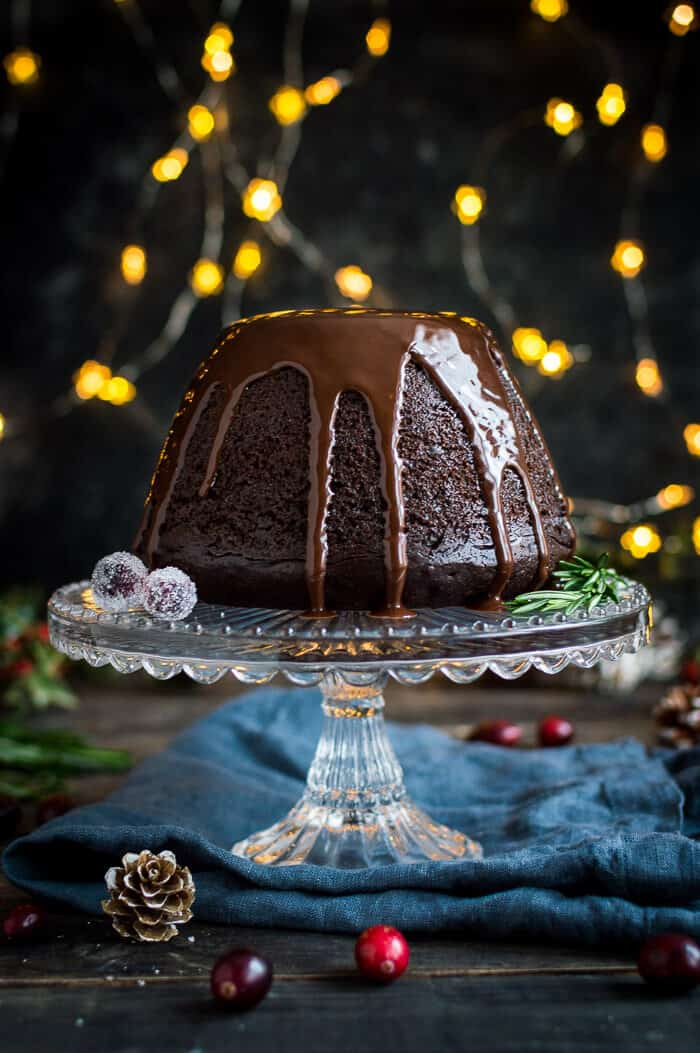 Vegan steamed chocolate pudding on a glass cake stand with fairy lights in the background.