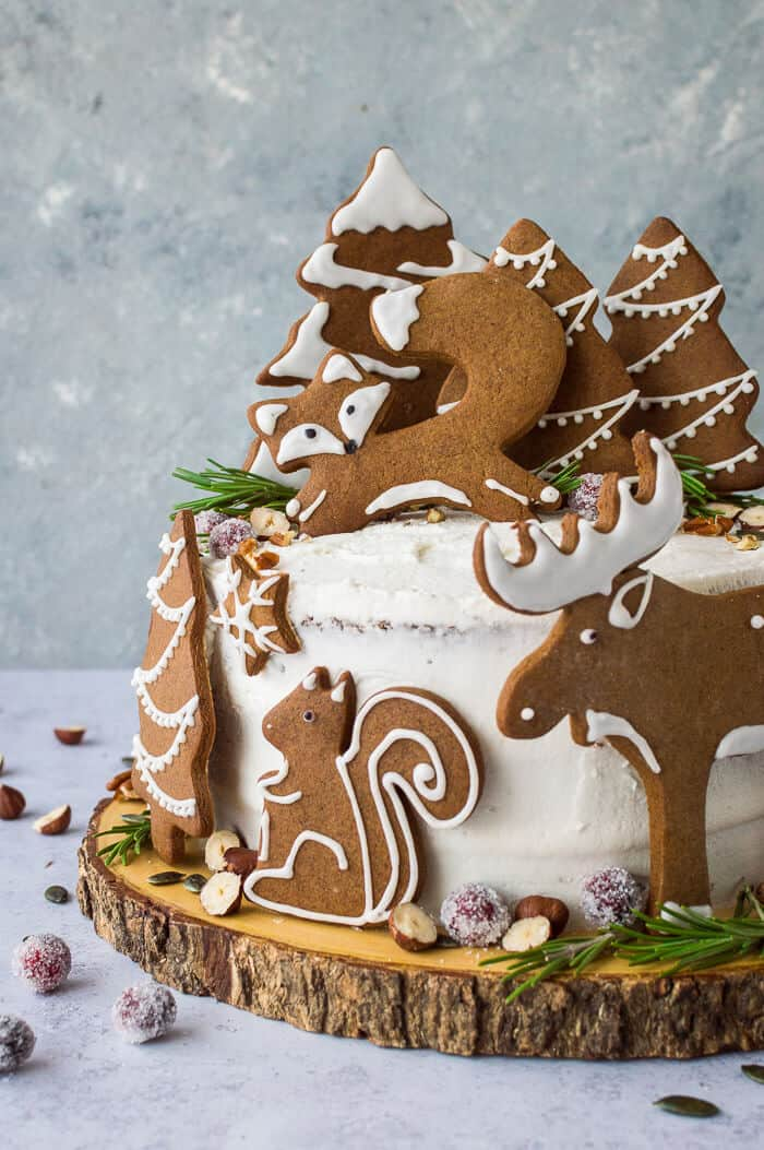 A side shot of vegan woodland animal ginger cake topped with gingerbread fox, squirrel, moose and trees.