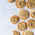 Vegan cinnamon swirl cookies arranged on a grey background with a bite taken out of one.
