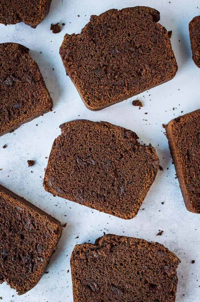 slices of vegan double chocolate banana bread arranged on a grey background