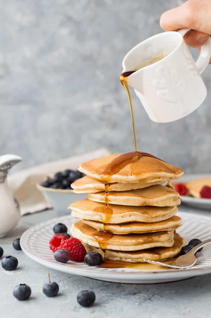 Maple syrup being poured onto a stack of fluffy vegan vanilla pancakes.