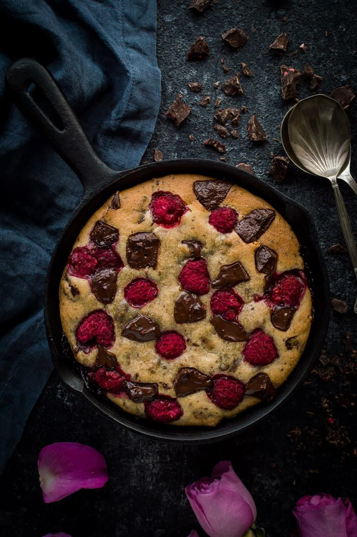 Chocolate raspberry skillet cookie for two on a black background with two spoons and a grey cloth.