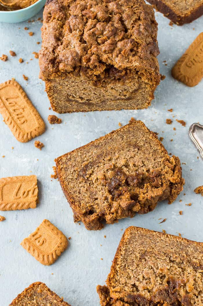 Angled shot of a loaf of sliced vegan biscoff banana bread with Lotus Biscoff biscuits.