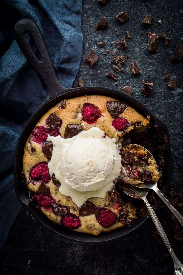 Chocolate raspberry skillet cookie for two - this indulgent vegan skillet cookie is really quick and easy to make, gooey in the middle and crisp around the edges. It is perfect for a romantic Valentine's day dessert to share! #vegan #skilletcookie