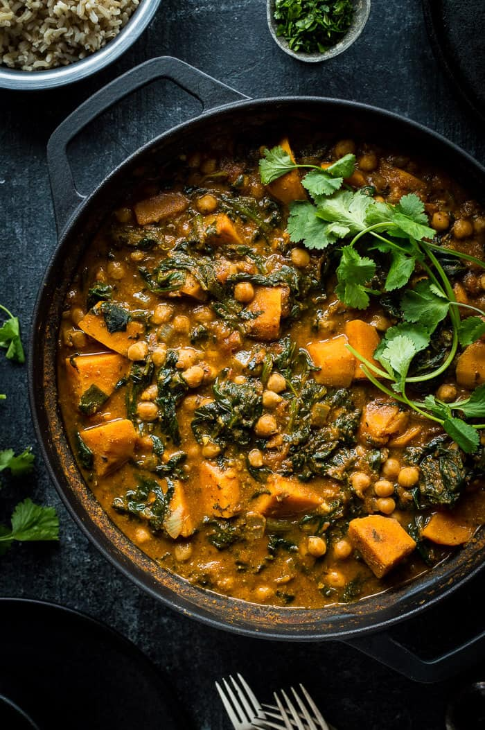 Close up of a black pan of vegan chickpea, sweet potato and spinach curry topped with fresh coriander.