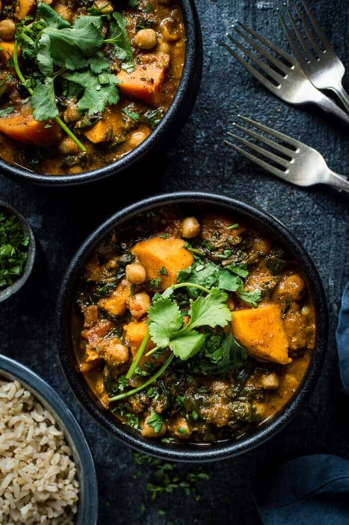 Two black bowls of vegan chickpea, sweet potato and spinach curry on a black background.