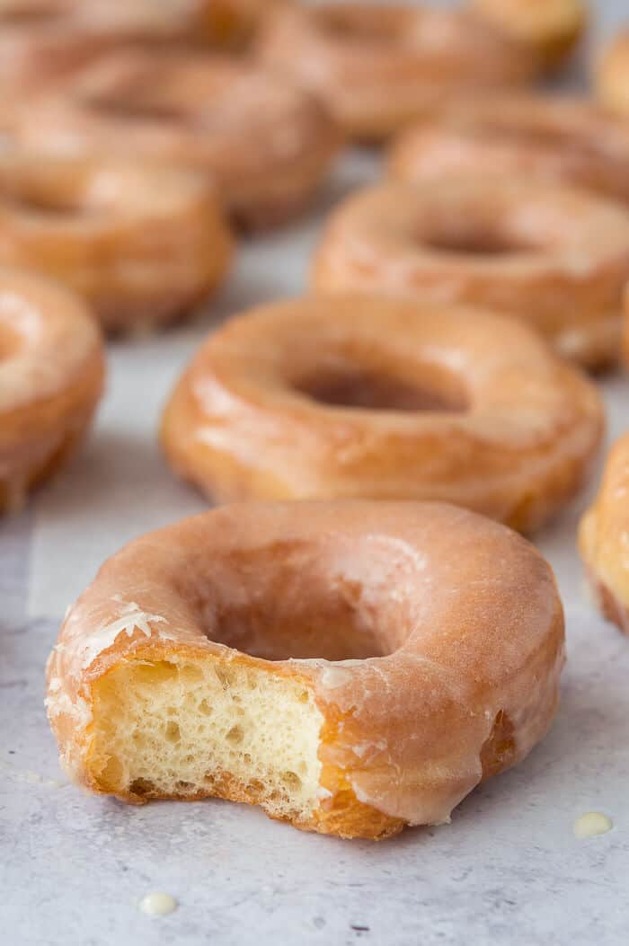 Vegan glazed doughnuts - these egg and dairy free fried ring doughnuts are incredibly light and fluffy. Topped with a vanilla glaze they are so moreish and very similar to a Krispy Kreme. #vegan #donut #doughnut