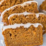 Close up of slices of vegan carrot cake loaf topped with lemon glaze.