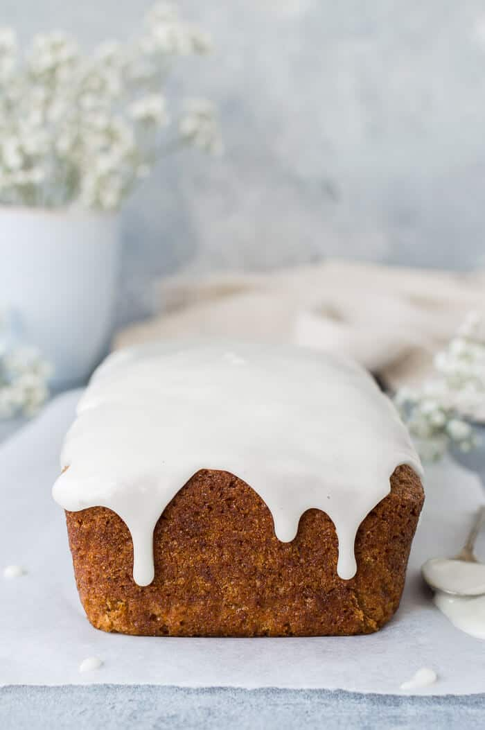Unsliced vegan carrot cake with lemon glaze on a sheet of baking parchment on a grey background with white flowers in the background.